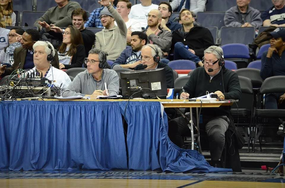 John Zannini '83, second from left, follows the action at a PC game at Georgetown. Alongside him are Friar basketball broadcasters Joe Hassett '77, third from left, and John Rooke, right.