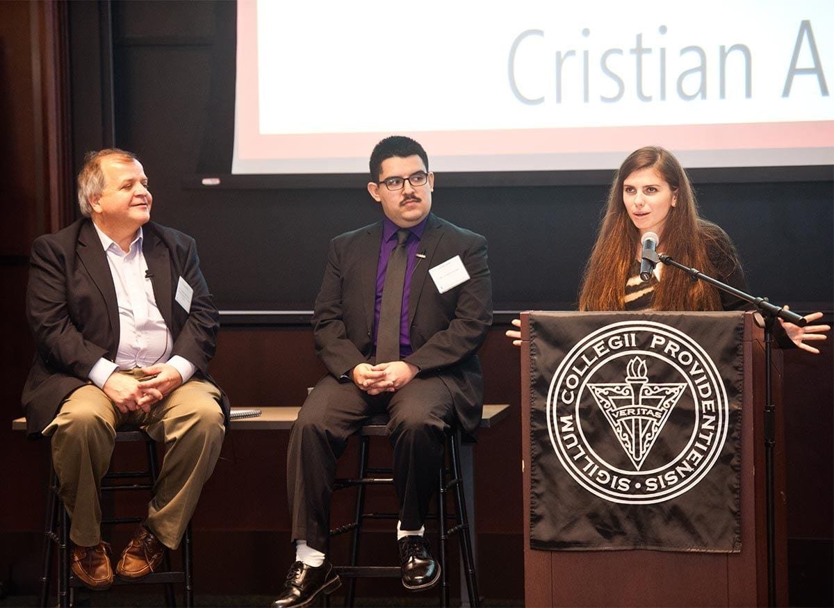 Claire Stover '21 introduces Cristian Arcega at the Faculty Experts Discussion. At left is Dr. Joseph Cammarano, assistant professor of political science and of public and community service studies.