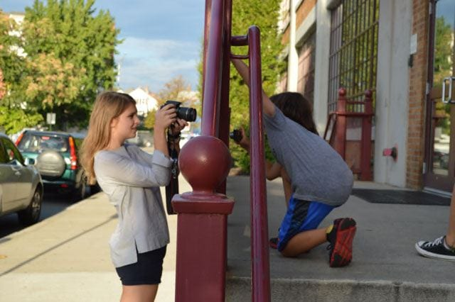Shannon Demers '21, left, shows a CityArts youth how to take pictures of subjects. Photo by Elizabeth Longo '21.