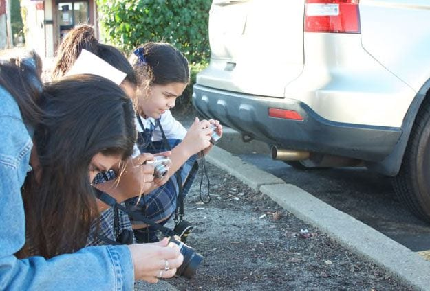 Kristen Lawler '18, left, shows two young artists how to zoom in and focus their cameras outside the Mount Pleasant Library. Photo by Payton Morse '20