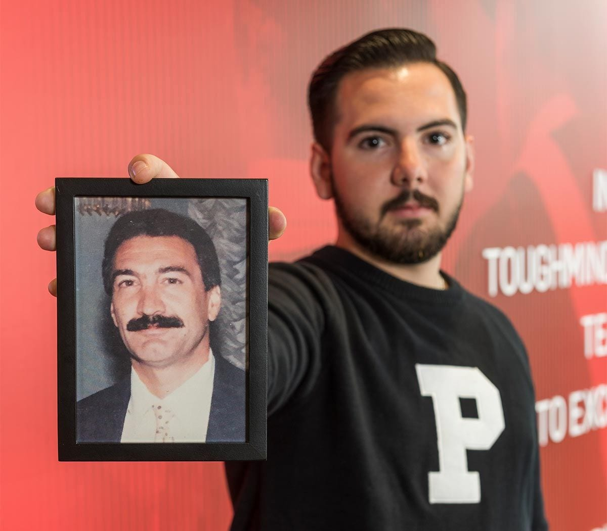 Joseph Padavano '17 holds a photo of his father, Louis, who died in 2011. Padavano and Everett Gabriel '71 & '77G both lost their fathers while in high school.