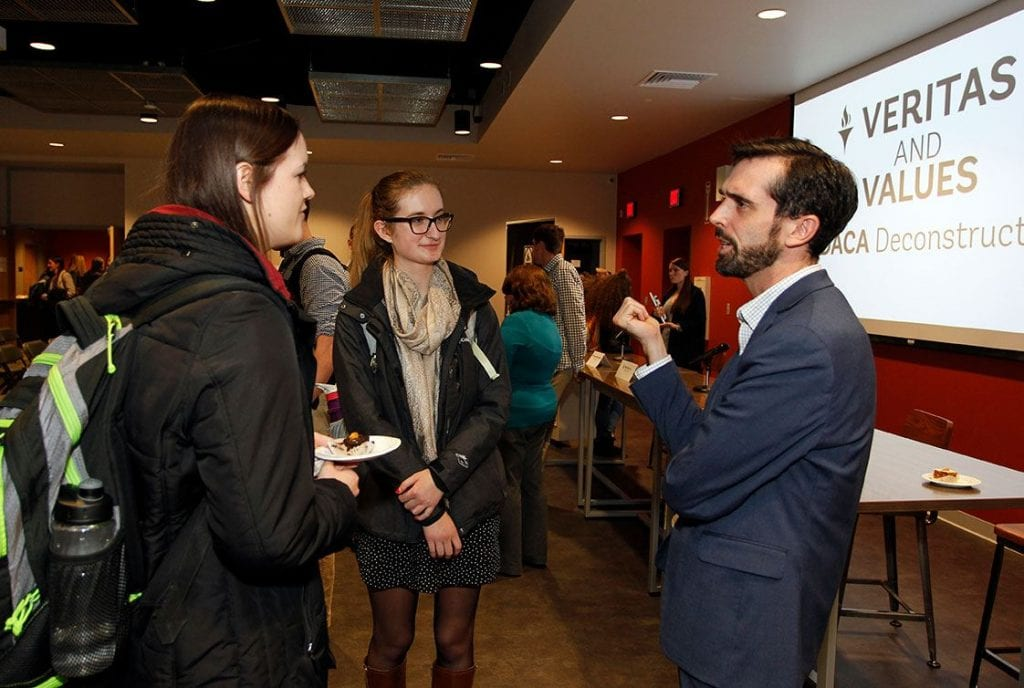 Panelist Mike Raia '05 speaks with Rachel Laravie '18, left, and Amy Gilligan '18 after the program.