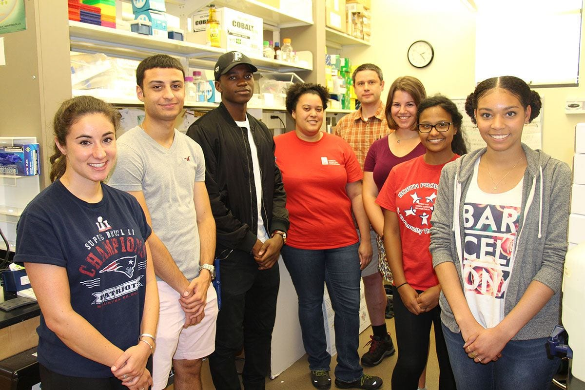 Dr. Cara Pina, fourth from left, and Dr. Brett Pellock, rear, are joined by several of their summer research students in the Pellock lab. From left are Ally Luongo '18, Ryan Silva '18, Dak Ojuka '20, Alexandra Shute '20, Nicole De La Rosa '18, and Winifer Rosario '17.