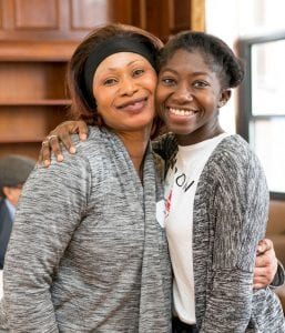Amie Mbye '18, right, gets a hug from her mother, Rose Lowe, at the 1G pinning ceremony for senior-class, first-generation students.