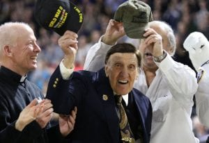 Ralph Paparella '40 waves his cap to the Dunkin' Donuts Center crowd, which stood to applaud his service in World War II. At left is PC President Rev. Brian J. Shanley, O.P. '80.