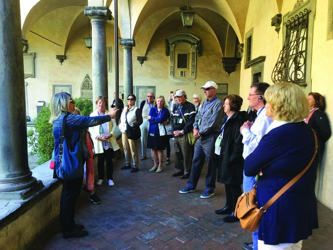 """The PC touring group listens to a local guide outside the cloisture of the Church of San Lorenzo in Florence during the """"Dominican Destinations"""" trip to Florence and Rome in fall 2017."""