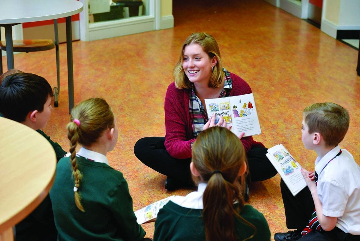 Student teacher Gabrielle Randall '19 works with students in a guided reading circle at the Dundonald Primary School in Belfast. (Photo by Aaron McCracken)
