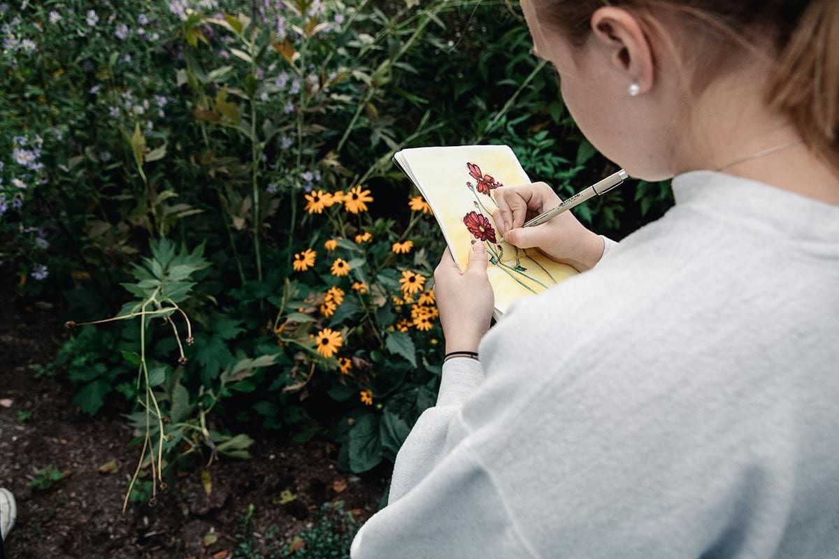 Emily McQuaid '19 adds to her colorful sketch of flowers in the bioswale.