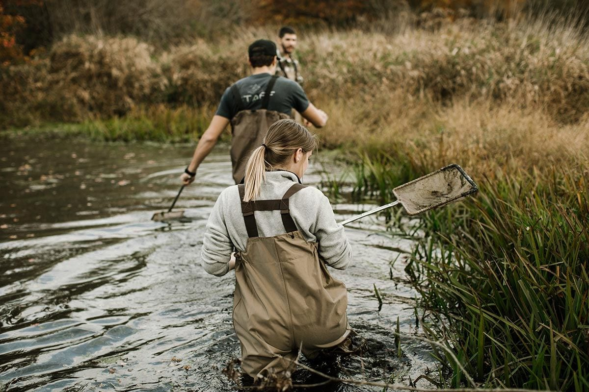 Wildlife Biology and Conservation students Sarah Mealey '17 and Peter Sanders '17 follow their professor, Dr. Jonathan Richardson, through a pond in Warren.