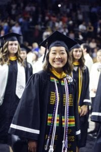 A graduate is all smiles as she processes into the arena with classmates.