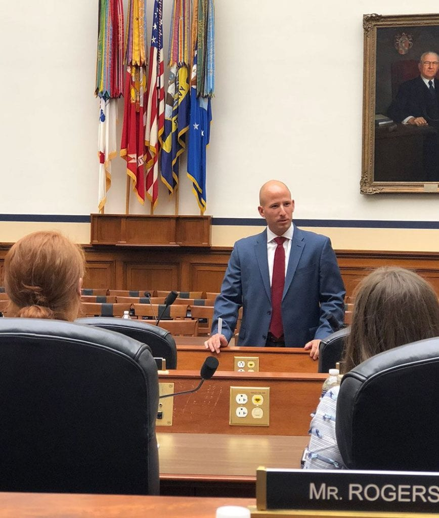 Major Michael Calcagni '04, a legislative liaison with the U.S. House of Representatives, speaks to fellows in a House meeting room.