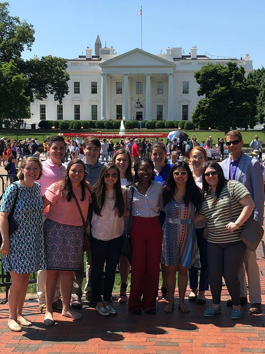 The PC in DC group stops briefly outside the White House. The group includes two of the co-directors of the Leadership Program, Leslie Heller '02, front left, and Dr. Matthew Eriksen, rear right. Students are, front row from left, Meredith Daigle '20, Devon Guanci '19, Phoebee Jean '19, Lianne Bisch '19, and Julia Vaccarella '20, and rear, Thomas McCormack '20, Dylan Black '20, Emily Kennedy '19, Morgan Starkey '20, and McKenzie Campbell '20.