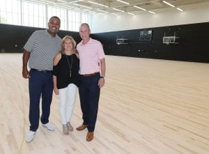 Karen and George Oliver join Ed Cooley, men's basketball coach, in the new basketball practice facility. One court is named for them.