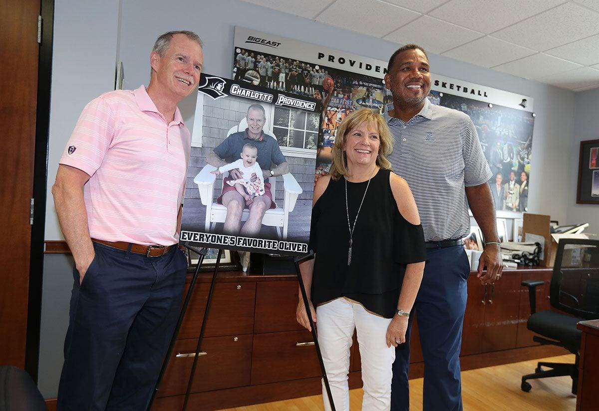 George and Karen Oliver during a visit to the office Ed Cooley, men's basketball coach. The poster is of their granddaughter, Charlotte Providence Oliver.
