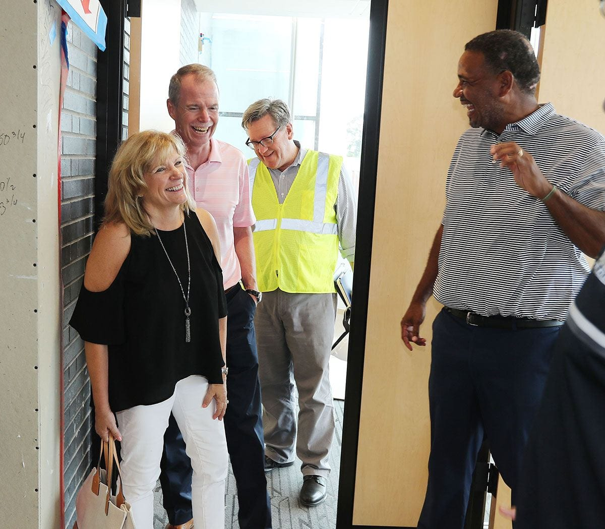Karen and George Oliver check out construction of the Ruane Friar Development Center with Ed Cooley, men's basketball coach. Following them is John Sweeney, PC's enior vice president and chief financial officer.