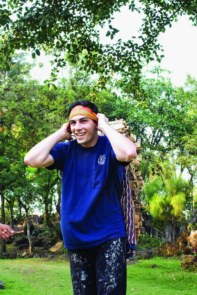 Luke Jenness '19 uses a traditional head strap to carry firewood. Highland Maya learn to carry wood this way from a young age.