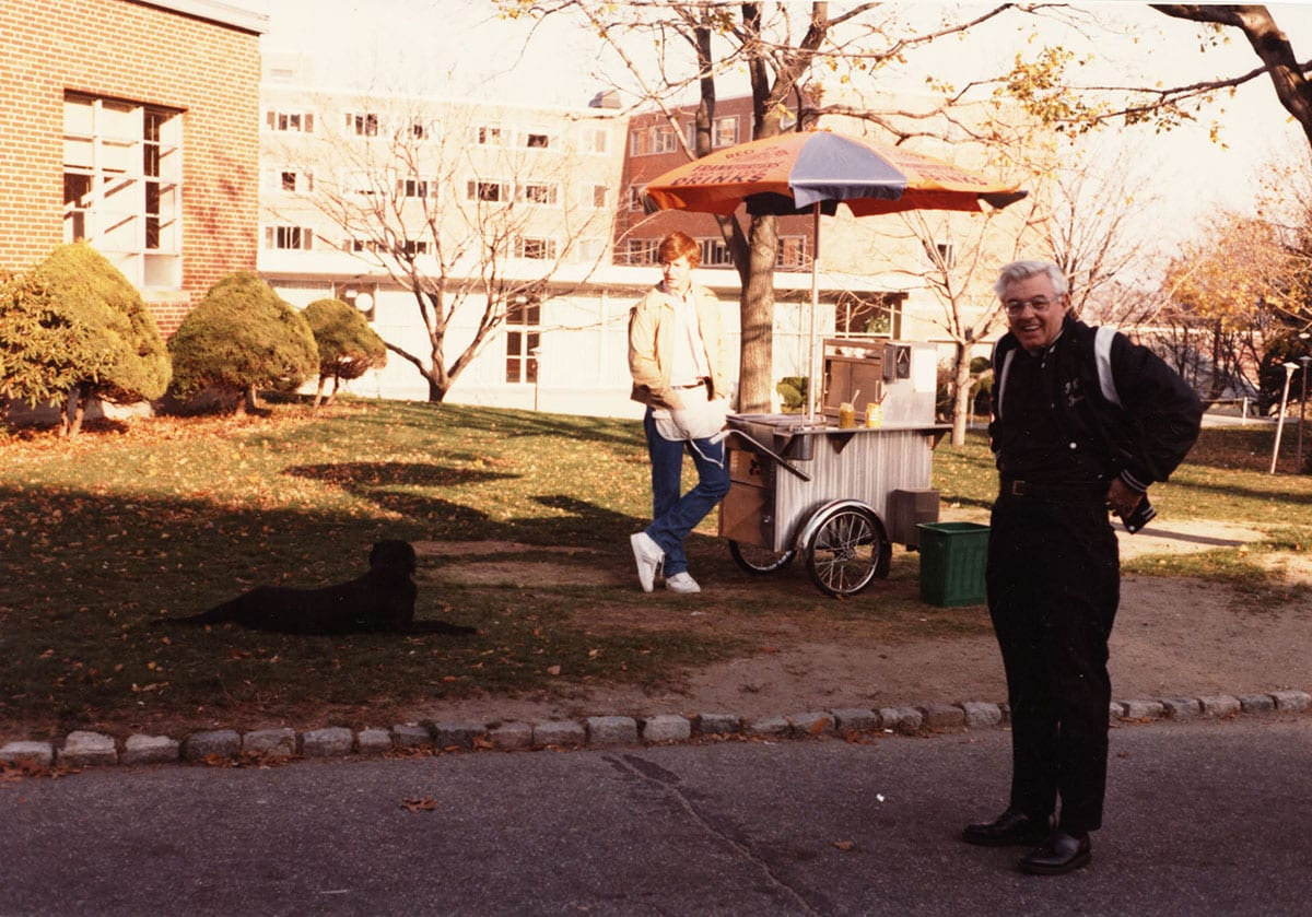Rev. Thomas J. Ertle, O.P. '53, '82G, & '84Hon., who died on Nov. 23, 2018, stands near the hot dog cart he pushed on campus while serving as the College's chaplain in 1980. His idea was to engage students walking across campus.