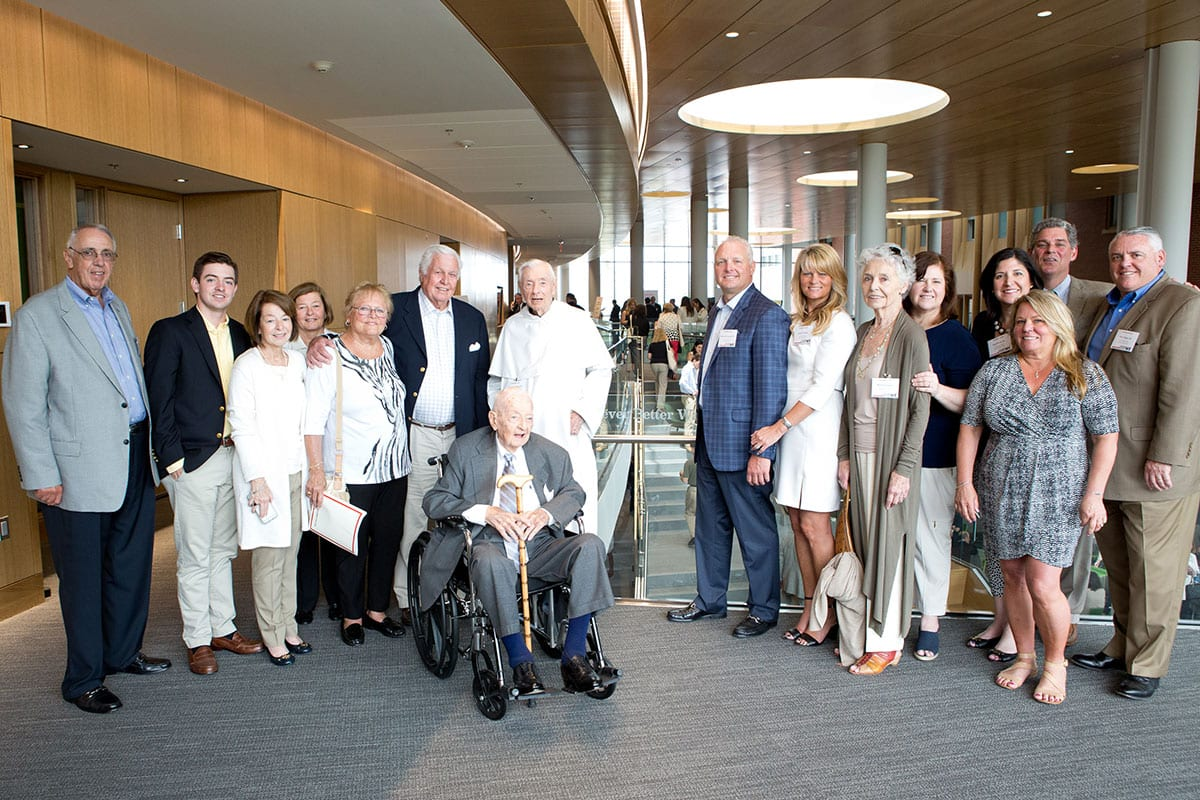 Father Ertle, at rear center, is joined by family members at the dedication of two walkways in his honor in the Arthur F. and Patricia Ryan Center for Business Studies in April 2017.