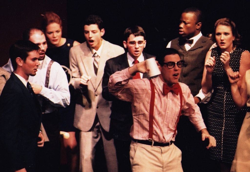"In his first year at Providence College, Dr. Troy Quinn '05 sang in musical ""How to Succeed in Business Without Really Trying."" He is fourth from left, in the tan suit."