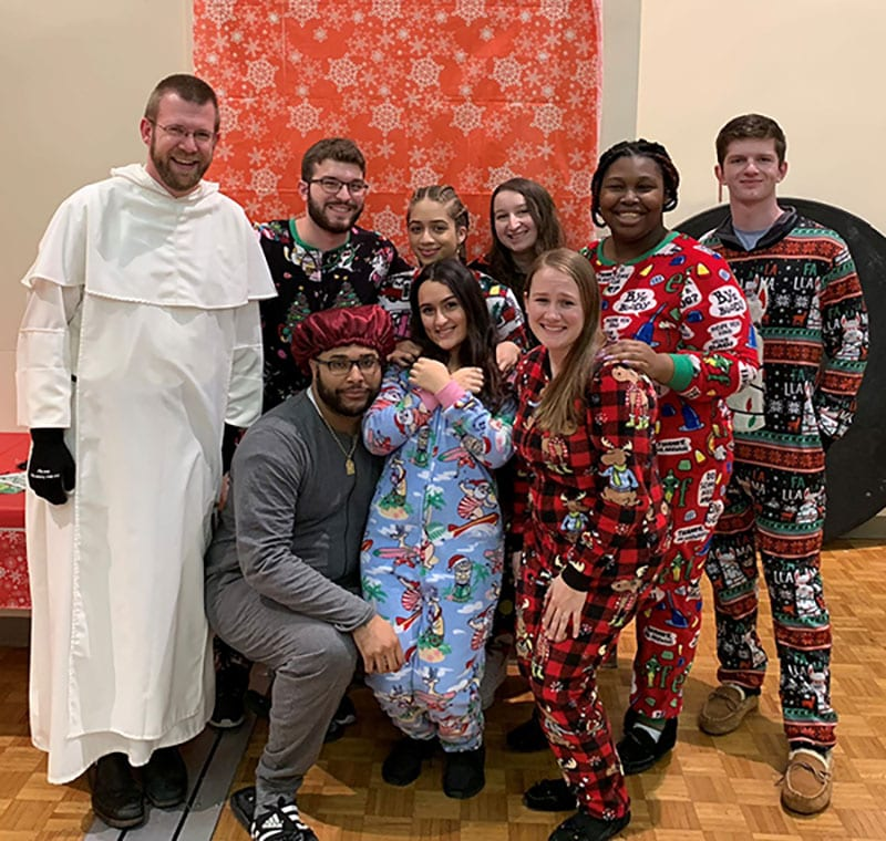 Rev. Vincent Ferrer Bagan, O.P., visiting faculty member in music and a residence hall chaplain, enjoys a Christmas celebration with residence life staff members from Bedford and Davis halls at the end of the fall semester.