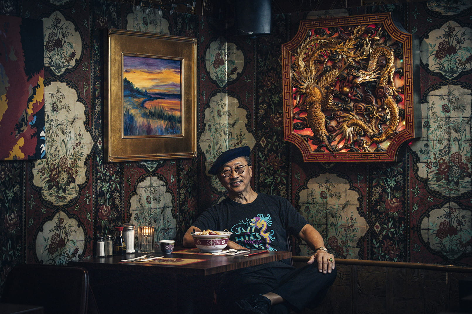 Wearing a shirt that advertises his restaurant as the home of jazz and blues, John Chan '74 poses in his restaurant dining room. One of his watercolor paintings is to his right.