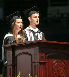 "Aisling Sheahan '19, left, and Evan Brandow '19 lead the ""Alma Mater"" at the conclusion of commencement."