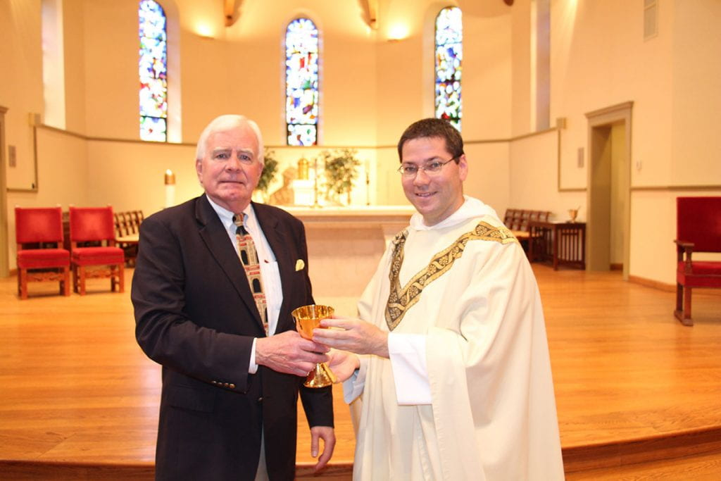 John G. Hussey '68, left, presents his brother's chalice to Rev. Peter Martyr Yungwirth, O.P., College chaplain.