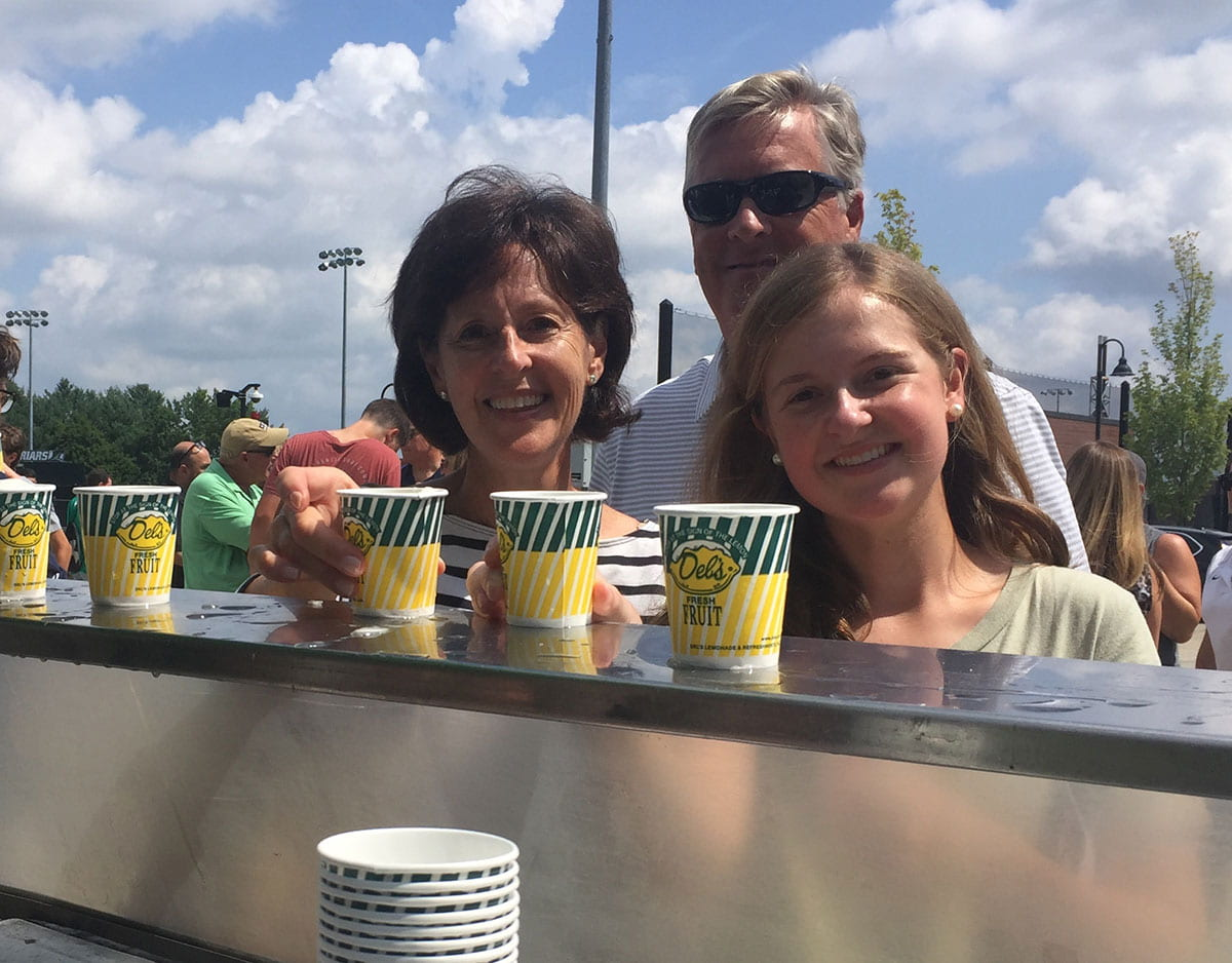 Caroline Lewers '23 and her parents pause for some Del's frozen lemonade at a cart manned by the Student Alumni Association. They are from Wayne, Pa.