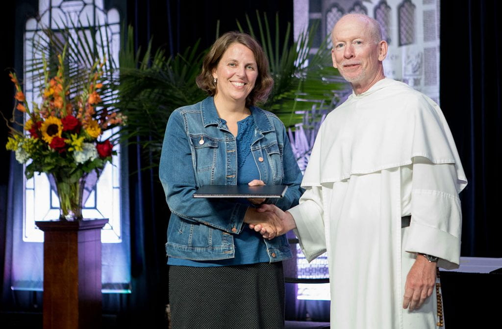 Dr. Marcy Zipke is congratulated by College President Rev. Brian J. Shanley, O.P. '80, upon her promotion to professor of elementary and special education.