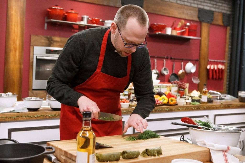Father Adam, wearing an apron, chops herbs on the Worst Cooks set.