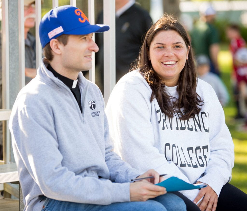 Erin O'Rourke '21, who interned with the Cape Cod League during the summer, takes in a game with her mathematics professor, Rev. Humbert Kilanowski, O.P.