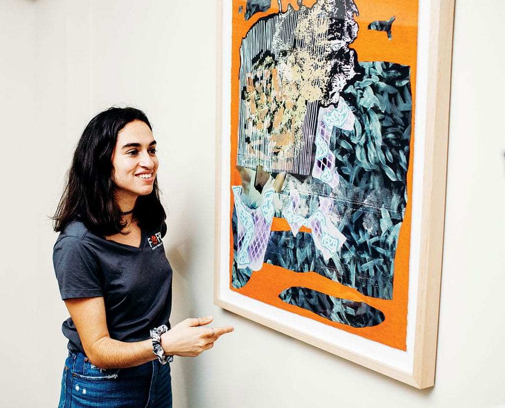 "Micaela ""Kit"" Freeman '20 stands next to a mixed-media work by Will Hutnick '07, a New York artist. Freeman worked for the PC Galleries in the summer of 2019 through an internship sponsored by Eric ""Pete"" Peterson '86 and Theresa Peterson '86."