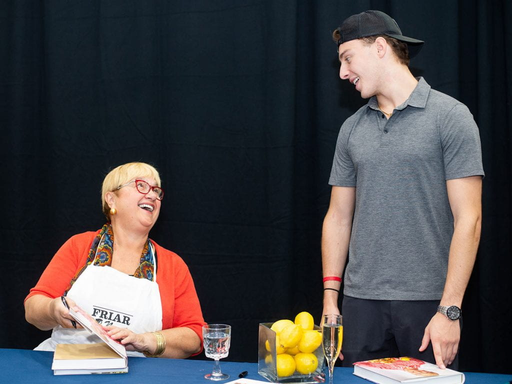 """Lida Bastianich exchanges a smile with her grandson, Miles Bastianich '22, as she signs copies of her book. She is wearing an apron that reads, """"Friar Nonni."""""""