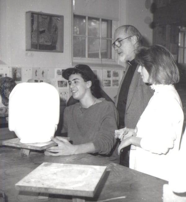 Father McAlister analyzes a sculpture with Timothy Jaccarino '92 and Kerri McGee '91 during a class.