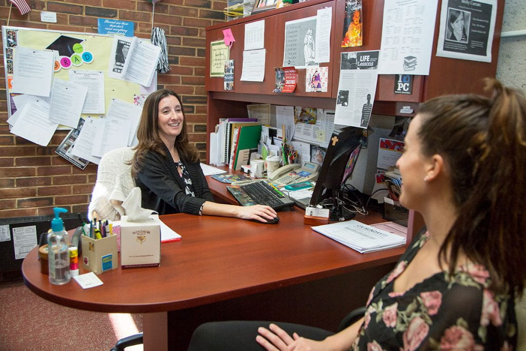 Jennifer Rivera '06 & '13G at work in her office in Phillips Memorial Library in 2016.