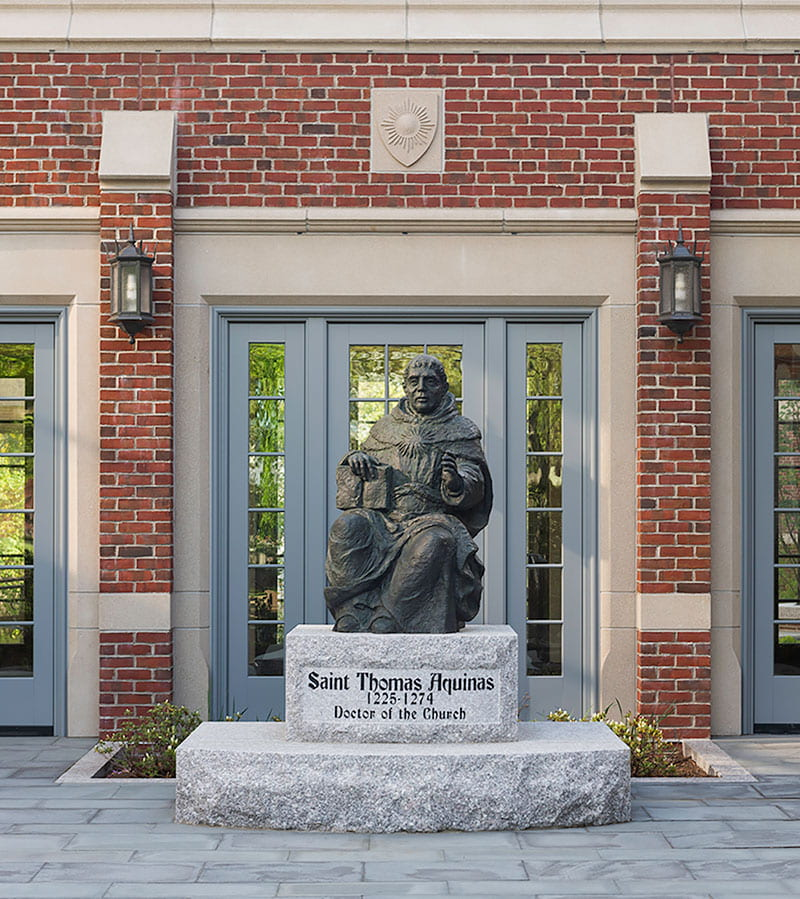 The life-size bronze statue of St. Thomas Aquinas, created by artist Sylvia Nicolas '01Hon., stands outside the connector linking the Ruane Center for the Humanities to Phillips Memorial Library.