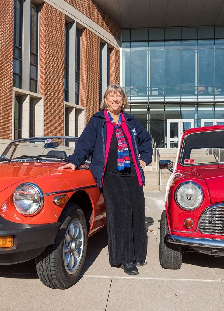 Faith Lamprey, a member of the full-time business faculty in accountancy, poses outside the School of Business with two of her cars, a 1980 MGB, left, and a 1967 Austin Mini.