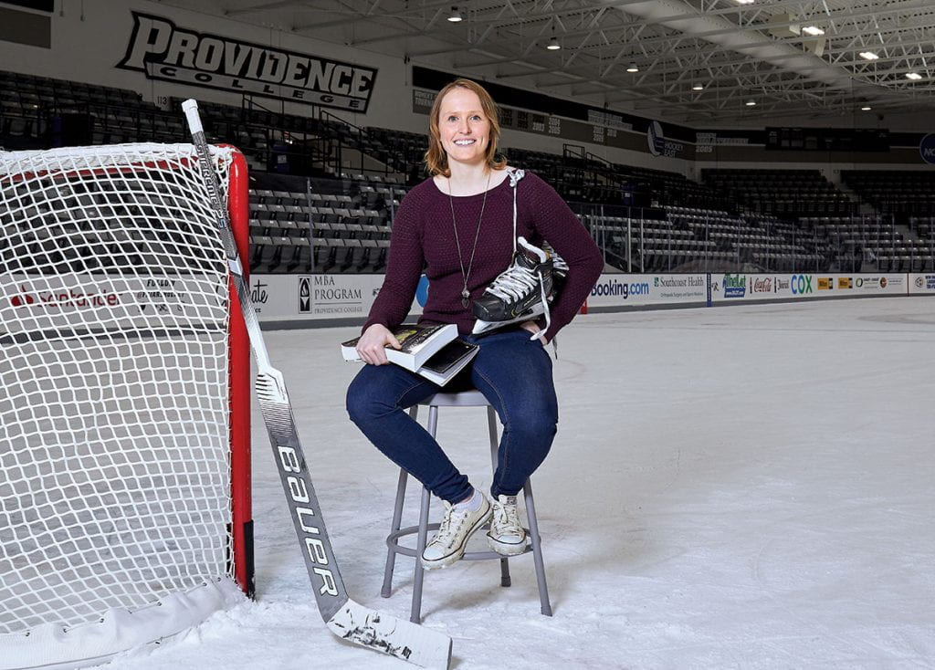 Clare Minnerath '20 sits on a stool on the ice at Schneider Arena with her hockey stick, skates, and books.