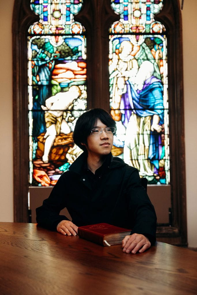 Tianyi Yuan '20 in the chapel of Guzman Hall with a stained glass window behind him.