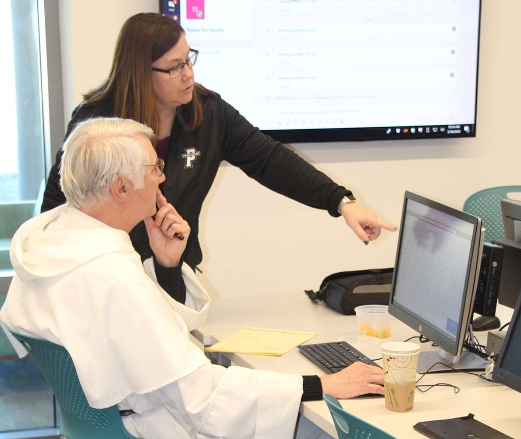 Donna J. Salisbury, software trainer and support specialist, advises Rev. John Vidmar, O.P., associate professor of history, during training to move courses online.