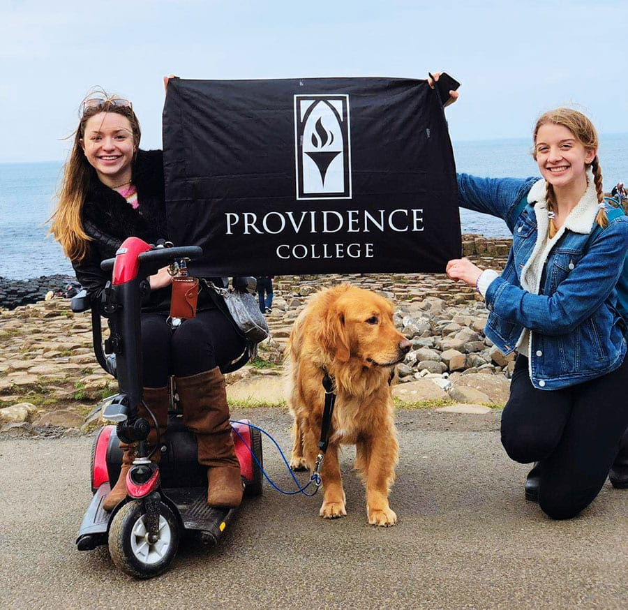 Jacquie Kelley '20, left, and Julia Gaffney '20 hold a Providence College flag during their semester abroad in Ireland.
