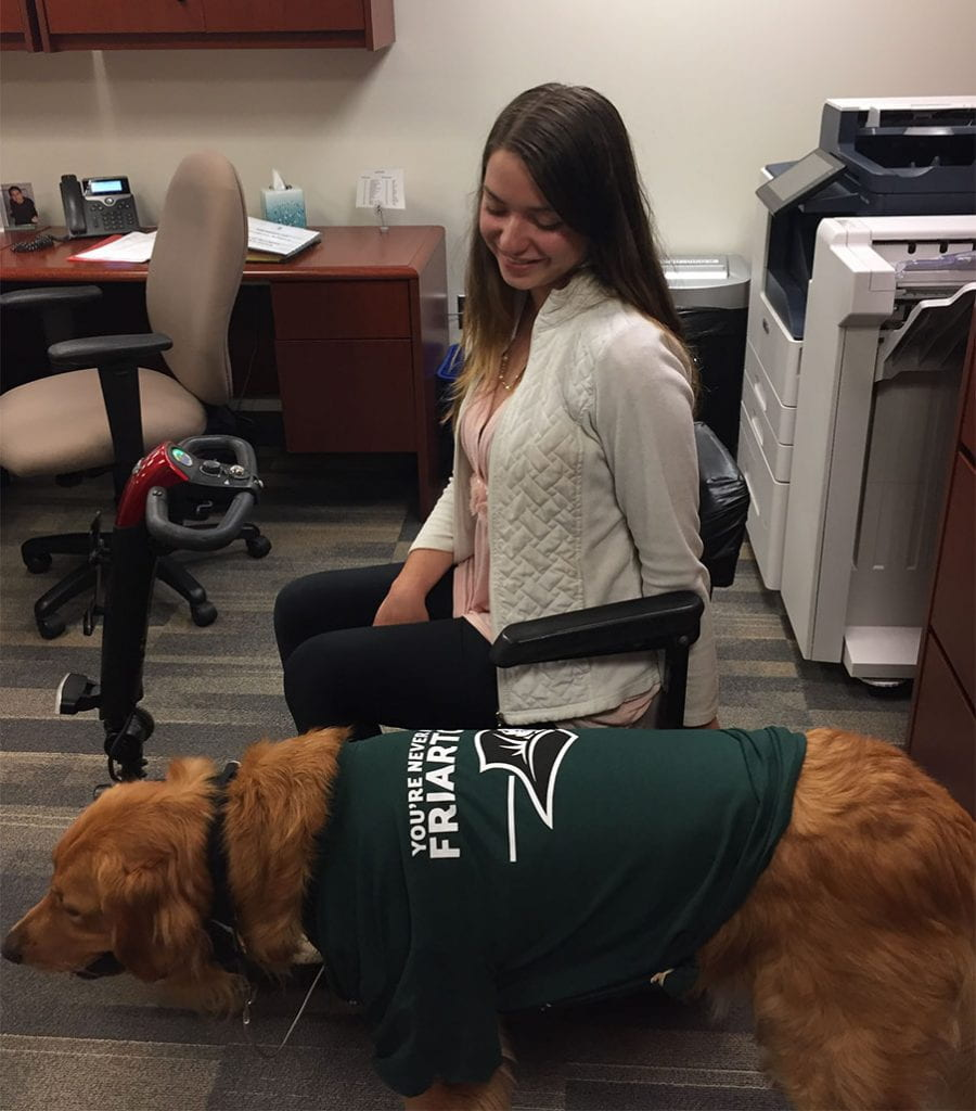 """Jacquie Kelley '20 and her service dog, Moose, helped the College with the marketing of Mental Health Awareness Month. Moose is sporting a """"You're Never Alone in Friartown"""" T-shirt."""