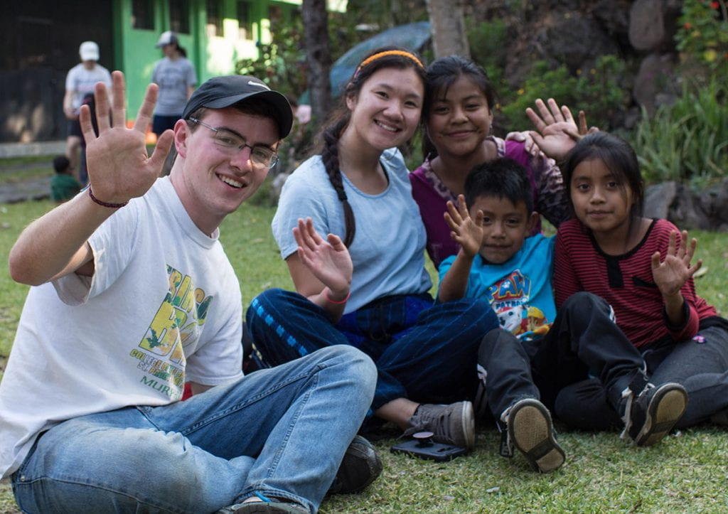 Jack Murphy '20 waves with Providence College students and children in Guatemala.