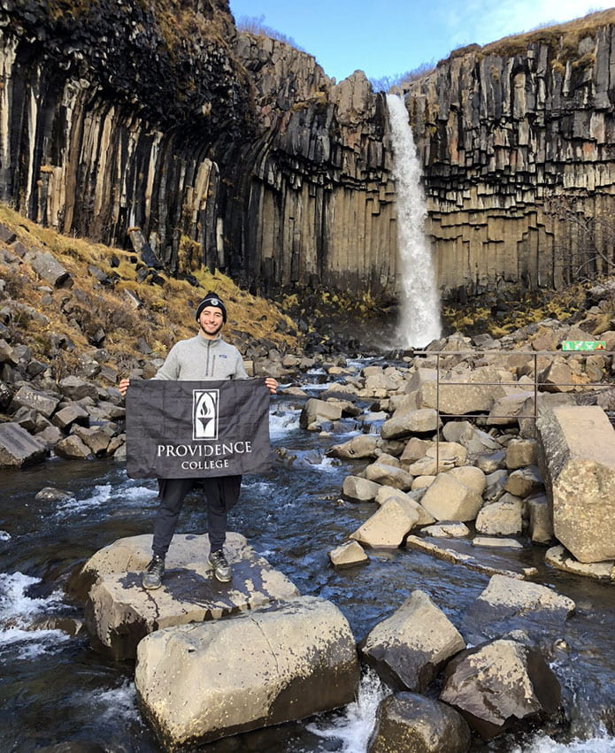 Nathan Perez '20 proudly displays a College flag at the Svartifoss waterfall in Iceland while studying abroad last fall.