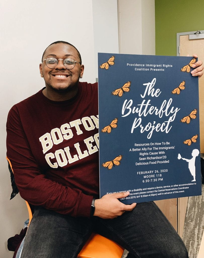 """Sean Richardson '20 holds a poster for """"The Butterfly Project,"""" an event related to his independent study research."""