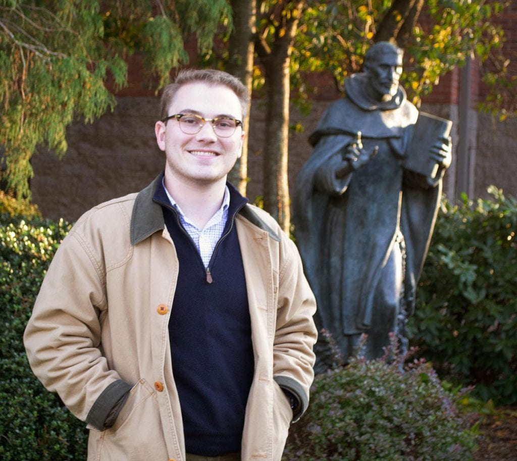 Sean Tobin '20, in front of the statue of St. Dominic on campus, will enter the novitiate of the Dominican Order's Eastern Province of St. Joseph in July in preparation for the priesthood.