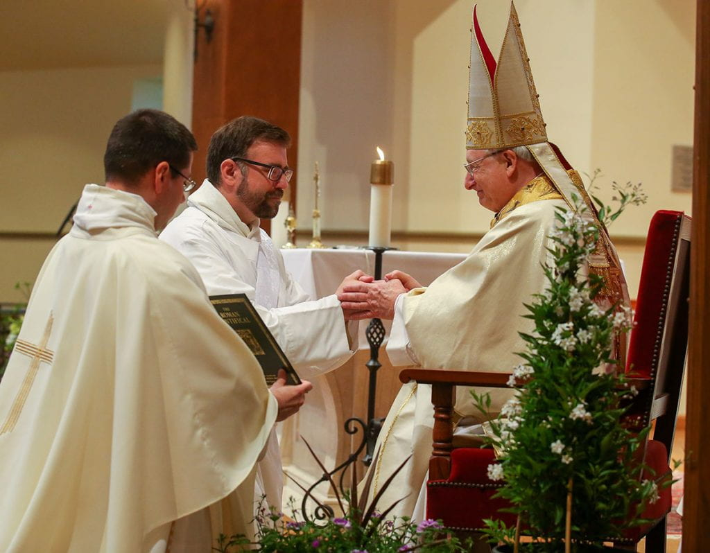 Brother Jordan Zajac, O.P. '04 kneels before Most Rev. Robert C. Evans, auxiliary bishop of Providence, and promises respect and obedience to the diocesan bishop and his religious superiors. Also pictured is Rev. Peter Martyr Yungwirth, O.P., College chaplain.