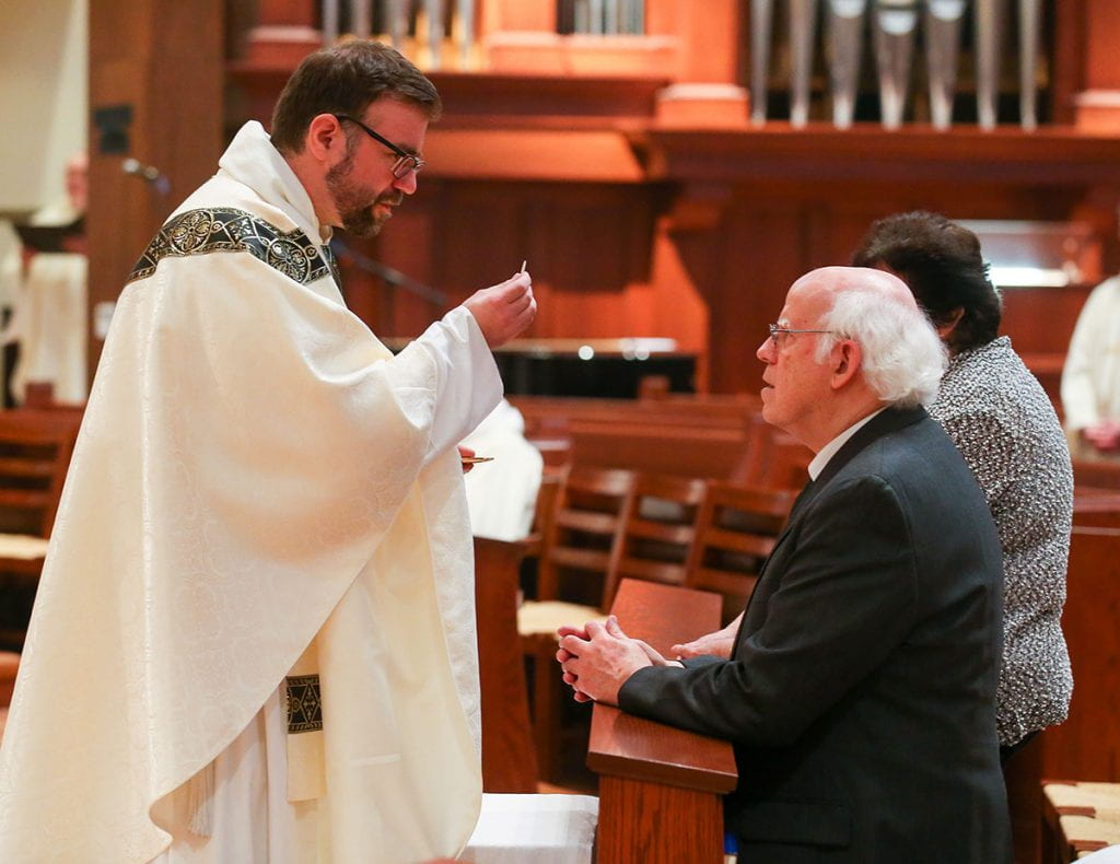 In his first act as a priest, Rev. Jordan Zajac, O.P. '04 offers the Eucharist to his parents, Peter and Judith Zajac.
