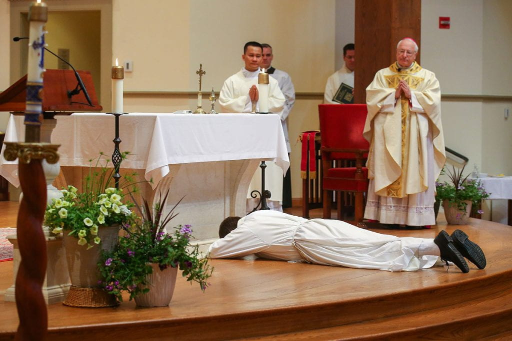Brother Jordan Zajac, O.P. '04 lies prostrate before the altar in St. Dominic Chapel, symbolizing his unworthiness for the priesthood and his dependence upon God and the Christian community. Standing are Deacon Hiep Nguyen, a seminarian who was ordained a priest in the Diocese of Providence on June 6, and Most Rev. Robert C. Evans, auxiliary bishop of Providence.