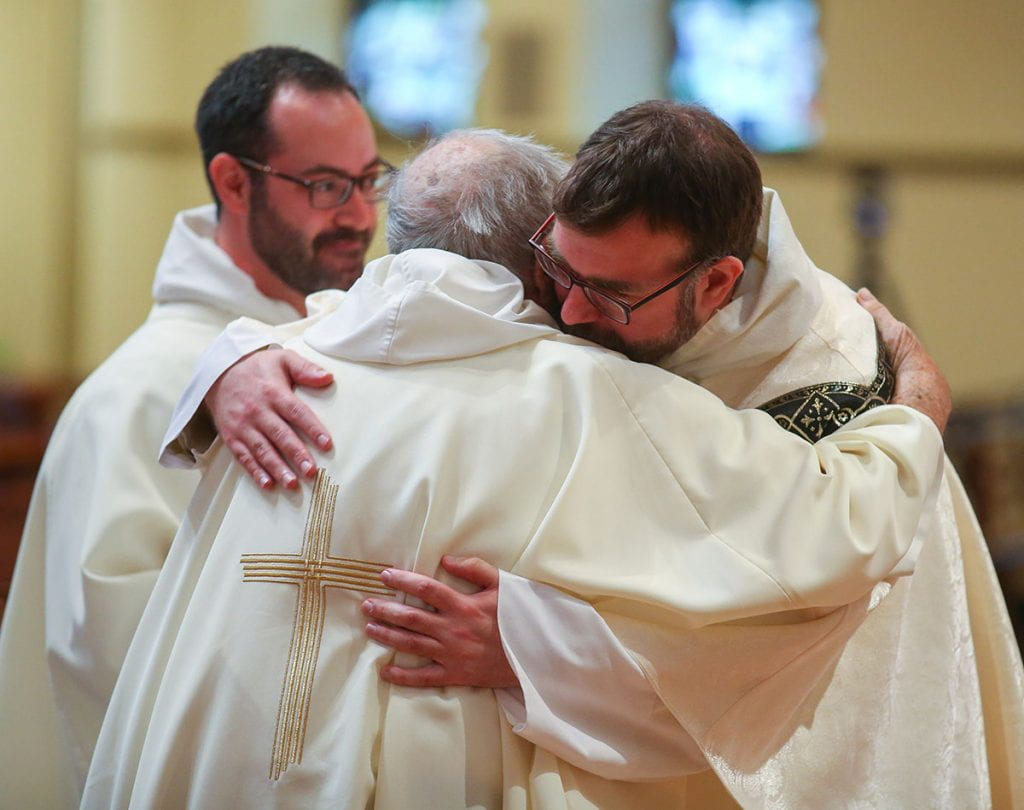 After being dressed in stole and chasuble for the first time, Rev. Jordan Zajac, O.P. '04 hugs his former theology professor, Rev. John Reid. Also pictured is Rev. Michael Weibley, O.P., assistant chaplain, who assisted.